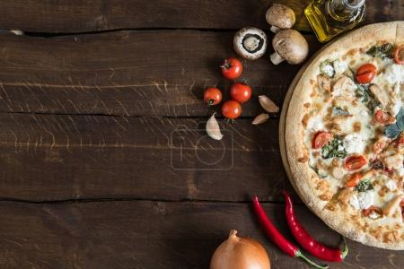 Photo for Top view of homemade italian pizza with various fresh ingredients on wooden surface - Royalty Free Image