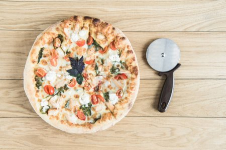 italian pizza with cutter on wooden tabletop