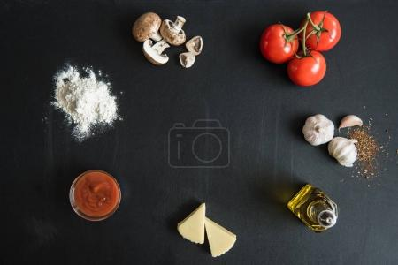 ingredients for preparing pizza on dark surface