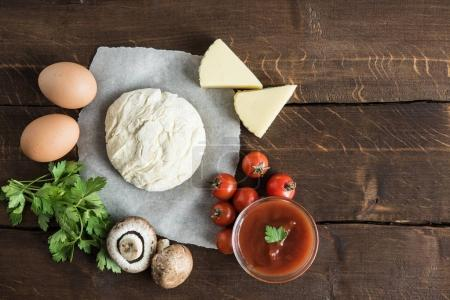 Photo for Top view of dough with ingredients for preparing italian pizza on wooden tabletop - Royalty Free Image