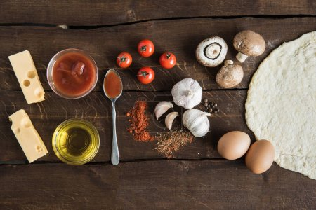 Ingredients for preparing pizza on wooden tabletop
