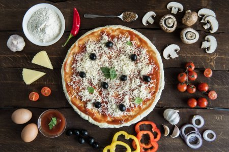 Photo for Top view of italian pizza with various ingredients on wooden tabletop - Royalty Free Image