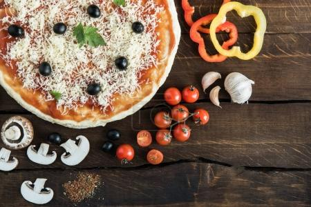pizza with cheese and vegetables on wooden tabletop