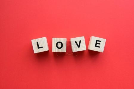 Photo pour Vue du dessus des cubes en bois avec signe d'amour sur fond rouge - image libre de droit