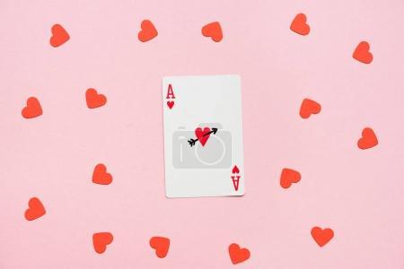 Photo pour As de cœur de carte à jouer avec des coeurs rouges qui traînent sur surface rose - image libre de droit
