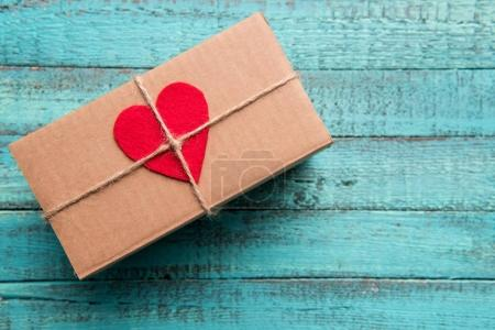 Photo for Top view of gift box with red heart on the top on wooden surface - Royalty Free Image