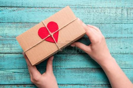 Photo for Above view of human hands holding gift box with red heart on the top on wooden table - Royalty Free Image