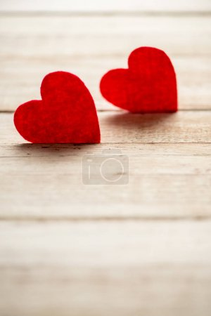 Red hearts lying on wooden table