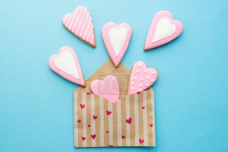 Photo for Open envelope with heart shaped cookies for Valentine day on blue surface - Royalty Free Image