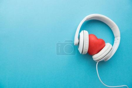Photo for White headphones with red heart sign in the middle on blue surface - Royalty Free Image