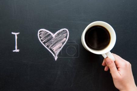 Photo for Top view of I love heart doodle drawing on chalkboard with human hand holding cup of coffee - Royalty Free Image