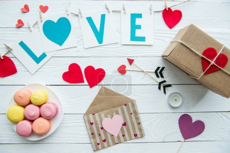 Photo for Top view of Valentines day decorations, macaroon cookies and gift box on wooden table - Royalty Free Image
