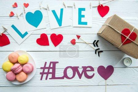 Photo pour Vue du dessus des décorations de la Saint-Valentin, des biscuits macarons, de la boîte cadeau et du signe du hashtag love sur une table en bois - image libre de droit