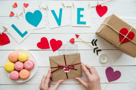 Photo for Above view of hands preparing gifts for Valentines day celebration with decorations and macaroons around on the table - Royalty Free Image