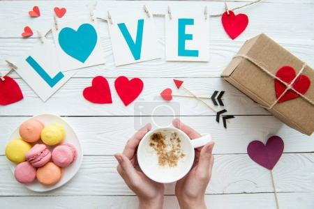 Photo for Top view of human hands holding cup of cappuccino with macaroon cookies, romantic decoration on wooden background. Valentines day composition - Royalty Free Image