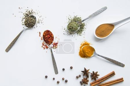 Photo for Top view of various dried aromatic spices in metal and ceramic spoons - Royalty Free Image