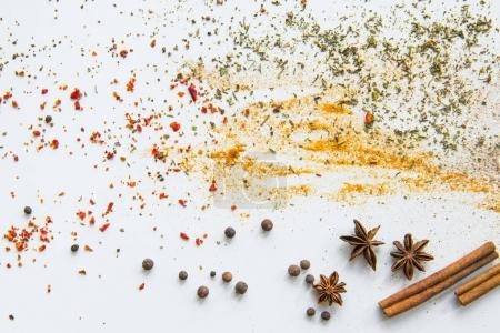 Photo for Close-up view of dried aromatic spices and herbs scattered on grey - Royalty Free Image