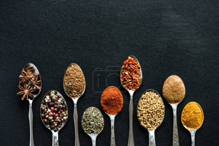 Photo for Top view of various spices and herbs in metal spoons isolated on black - Royalty Free Image