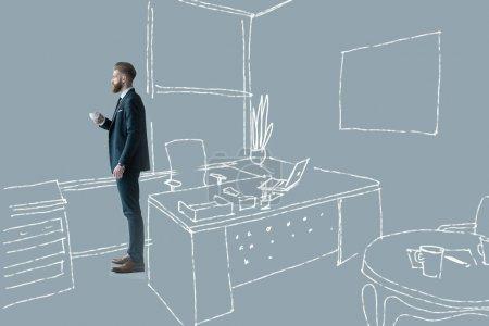 Photo pour Vue latérale de l'homme d'affaires en costume élégant tenant tasse de café au bureau dessiné - image libre de droit