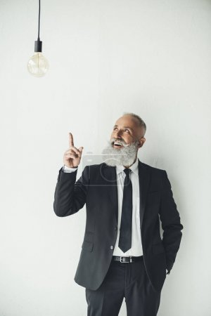 Photo for Senior businessman pointing at idea light bulb on light background - Royalty Free Image