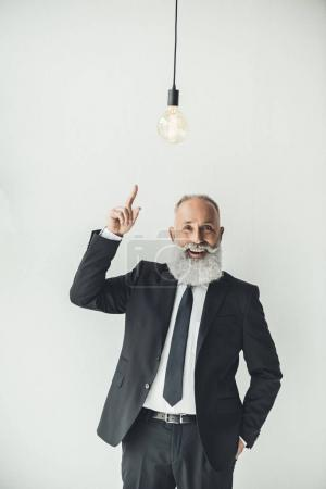 businessman pointing at light bulb