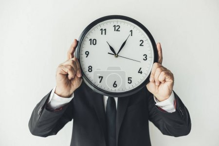 Man covering face with clock
