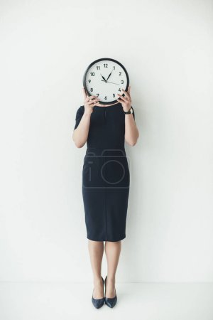 Woman covering head with clock