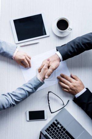 Photo pour Vue de dessus des gens d'affaires se serrant la main au cours de la réunion - image libre de droit