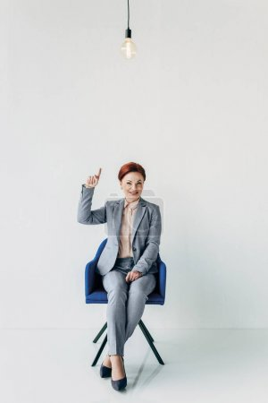 businesswoman pointing at light bulb