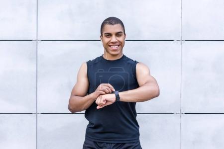 african american sportsman using smartwatch