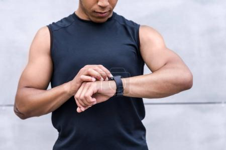 Photo for Cropped shot of young african american sportsman using smartwatch - Royalty Free Image