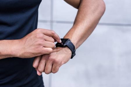 Photo pour Plan recadré de sportif afro-américain en utilisant smartwatch - image libre de droit