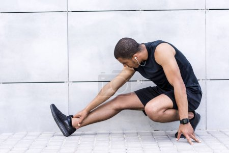 Photo for Young african american sportsman stretching legs and listening music in earphones - Royalty Free Image