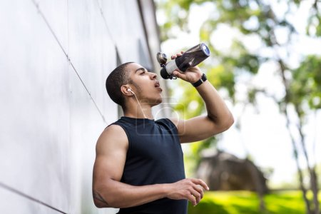 african american sportsman drinking water