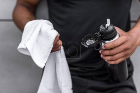 sportsman with sports bottle and towel