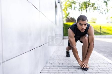 african american sportsman stretching on street