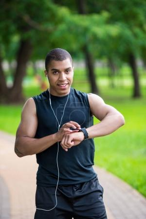 african american sportsman using smartwatch