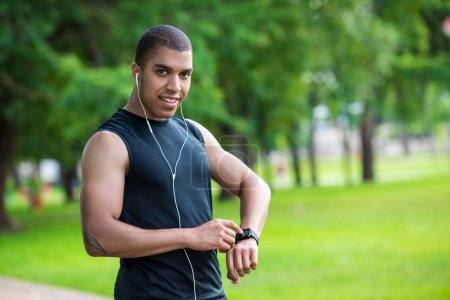 Photo for Young african american sportsman using smartwatch and smiling at camera in park - Royalty Free Image