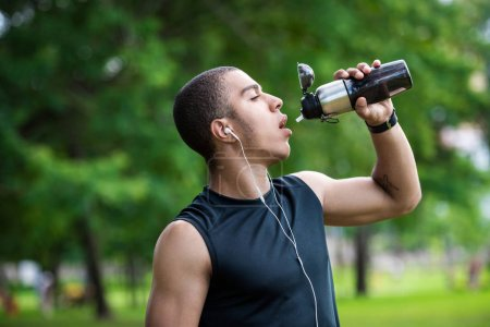 Photo for Handsome young african american sportsman drinking water from sports bottle in park - Royalty Free Image