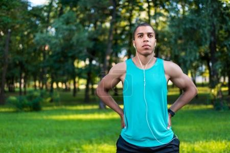 Photo for Pensive young african american sportsman stretching in park - Royalty Free Image