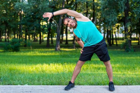 african american sportsman stretching in park
