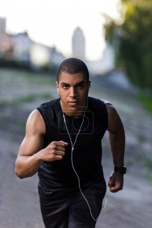 african american sportsman running on street