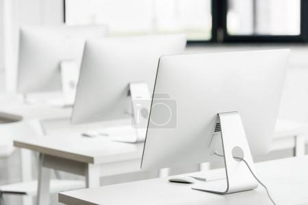 computer monitors on tables in class