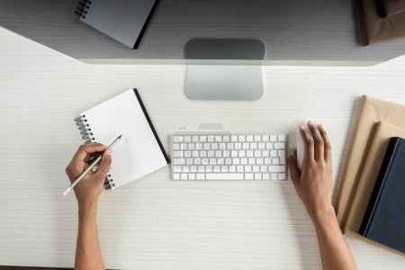 Photo for Partial view of student writing in notebook and using digital devices while doing homework - Royalty Free Image