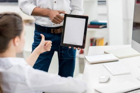 girl showing thumb up to classmate with tablet