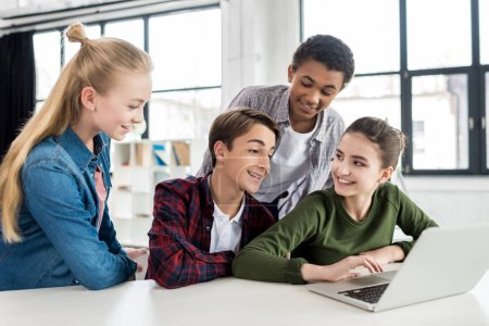 Photo for Multiethnic group of teenagers using laptop together in class - Royalty Free Image