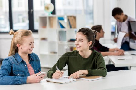 Photo pour Heureuse caucasiennes adolescentes regardant les uns les autres alors qu'ils étudiaient ensemble en classe - image libre de droit