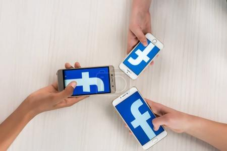 Photo for Cropped shot of teenagers holding smartphones with facebook logo on screens in hands - Royalty Free Image
