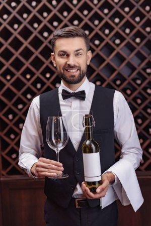 Photo pour Portrait de sommelier beau tenant bouteille de vin et verre en cave - image libre de droit
