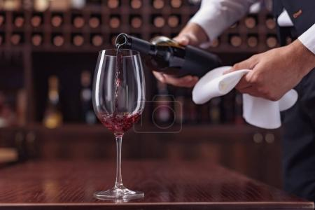 Photo pour Sommelier vue sur la récolte versant le vin rouge de la bouteille dans le verre à la table dans la cave - image libre de droit